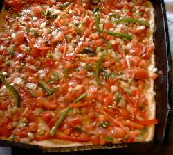 Pizza de masa con panceta y cubierta con salsa de atún