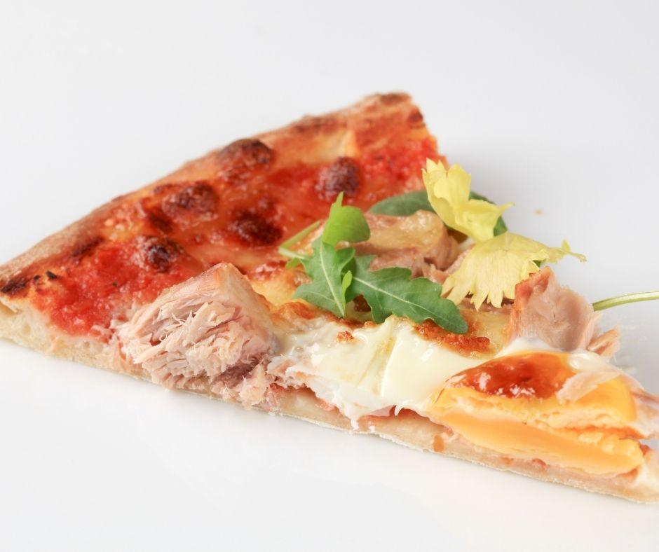 Dos pizzas en una, sardina, huevo duro, mayonesa; otra de atún con salsa de tomate y ricota
