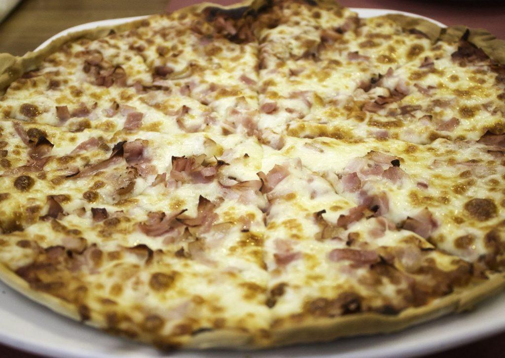 Pizza con panceta (bacón) tostada, salsa, cebolla y mozzarella