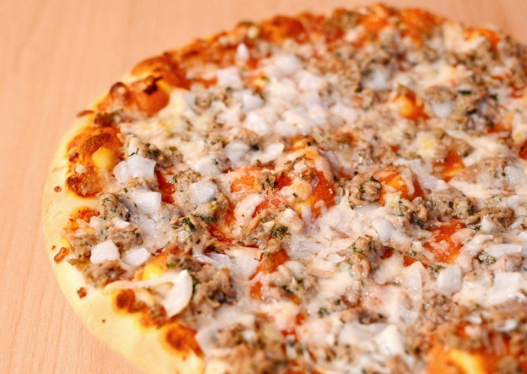 Pizza con panceta en la masa y cubierta con salsa de atún