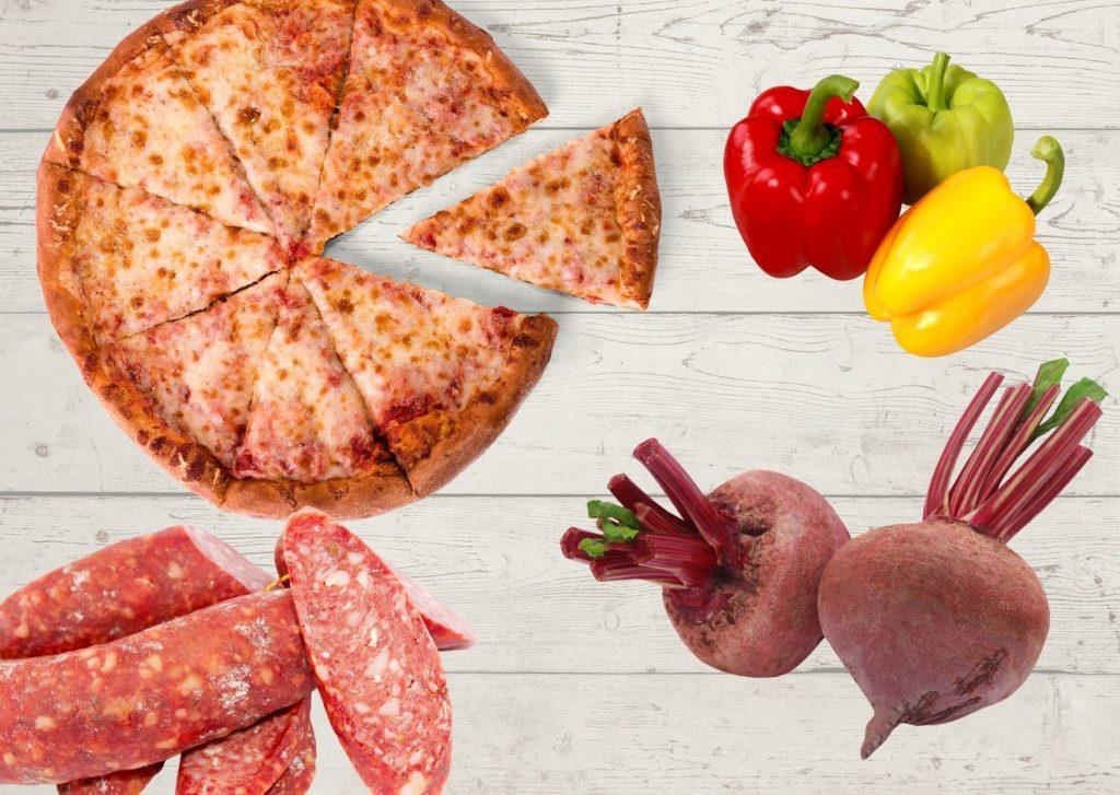 Pizza con masa roja de remolacha y cubierta de longaniza y morrón adobado