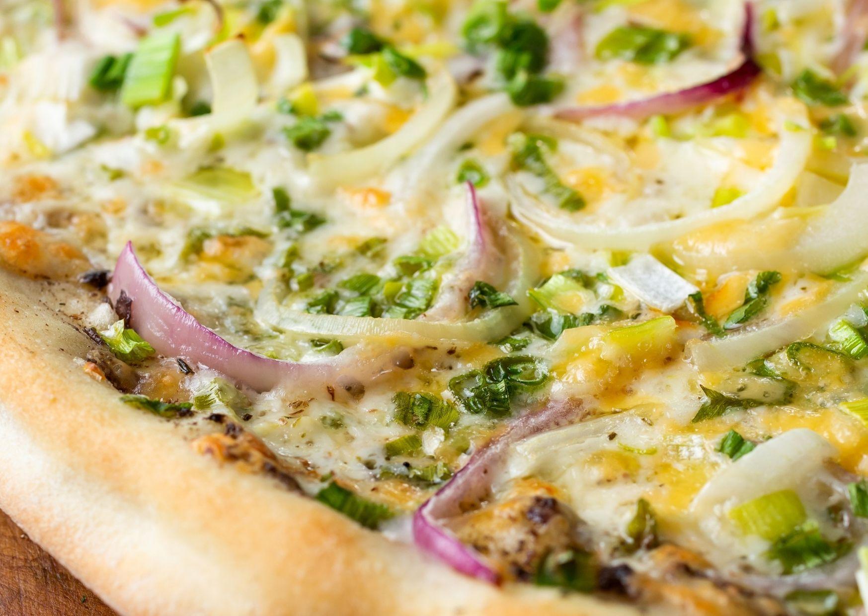 Pizza distinta con mucha cebolla y queso