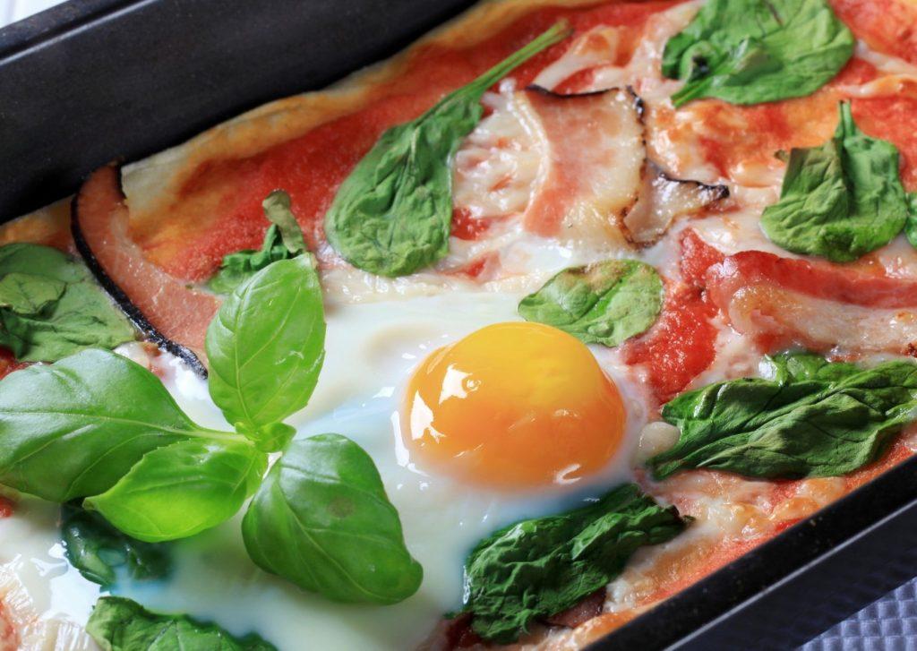 Pizza con cubierta de acelga, huevo, queso, panceta